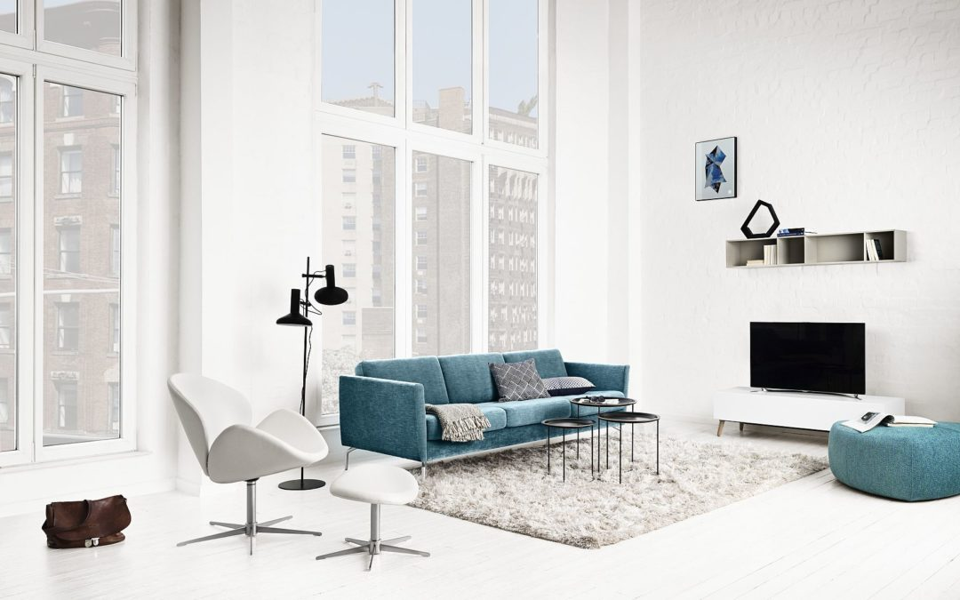 Blue 3-place sofa and a white armchair with a footstool by BoConcept